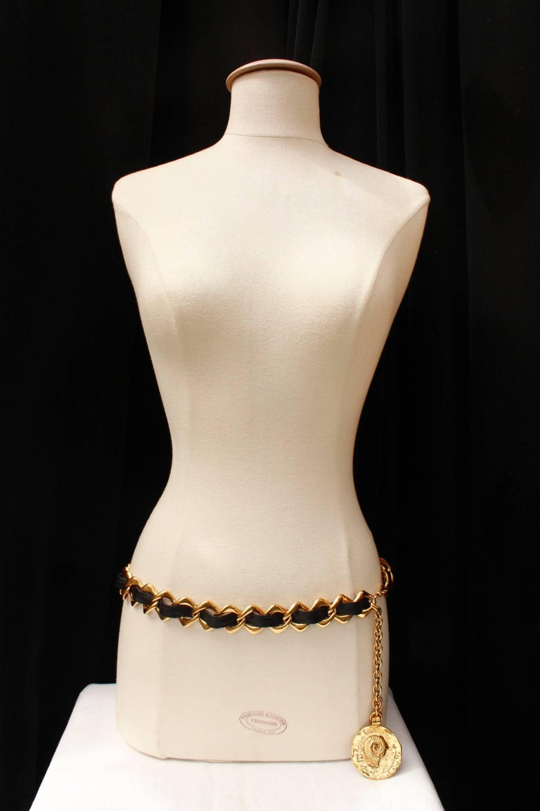 YVES SAINT LAURENT (Made in France) – Belt composed of a wide openwork gilded metal rhomboid chain entwined with a wide black leather strip. It is adjustable by means of a long gilded metal chain ending with a round hammered pendant decorated with a