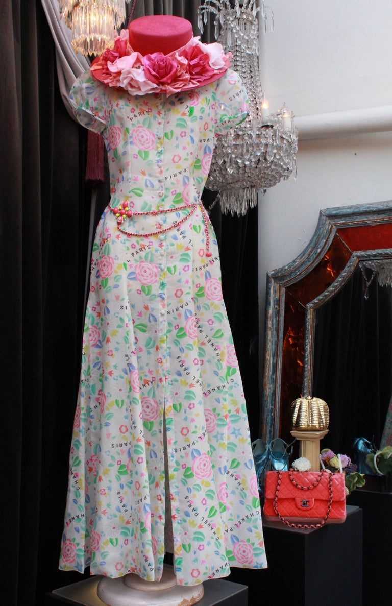 """CHANEL (Made in France) – Long shirt dress made of white silk organza., with floral print representing camellias in light green, blue, yellow and pink tones. """"Chanel Paris"""" reads in black letters throughout the print. The dress features a cinched"""