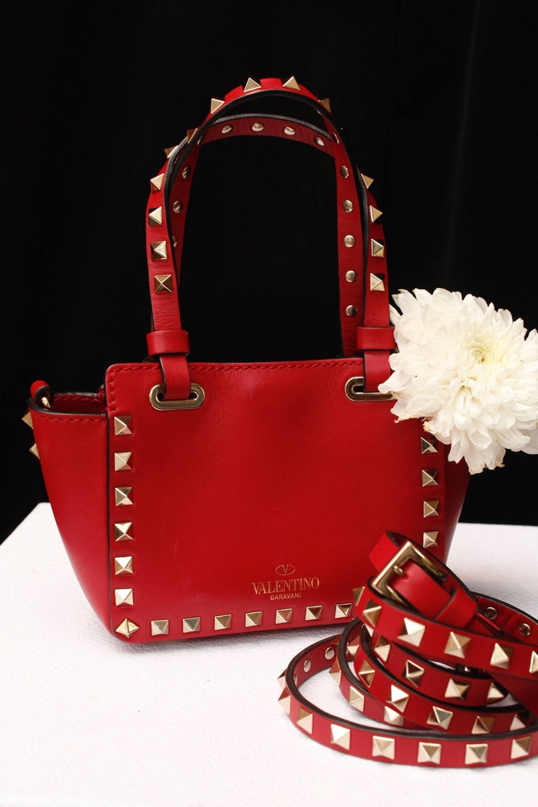 VALENTINO GARAVANI (Made in Italy) Magnificent mini Rockstud tote in bright red leather featuring gold tone diamond-shaped studs, round handles and a removable shoulder strap. Cream fabric lining.  Circa 2010.  Serial number BG-L088BOL2.  Width 16