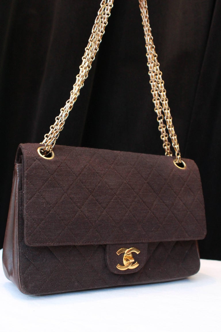 "CHANEL (Made in France) Very nice brown ""Timeless"" vintage bag, in brown leather and over stitched cotton. It features a double sliding shoulder strap to wear ""cross-body"" or over the shoulder. Gilded metal kiss-lock. Brown fabric lining. One zipped"