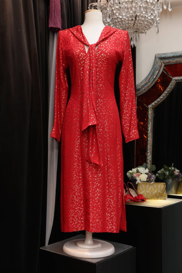 YVES SAINT LAURENT RIVE GAUCHE (Made in France) Beautiful red silk cocktail dress with long sleeves and V-neck.It is printed with leopard patterns embroidered with gold lurex. A  stitched strip of fabric at the neck adds a touch of scarf-like