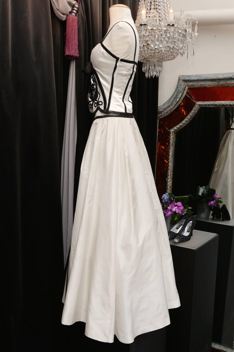 LORIS AZZARO (Attributed to) Gorgeous set made of white silk taffeta. The thin strap bustier is embroidered with sequins and black beads at collar and bust in a floral pattern. The center is embellished with a wide black satin bow and a large