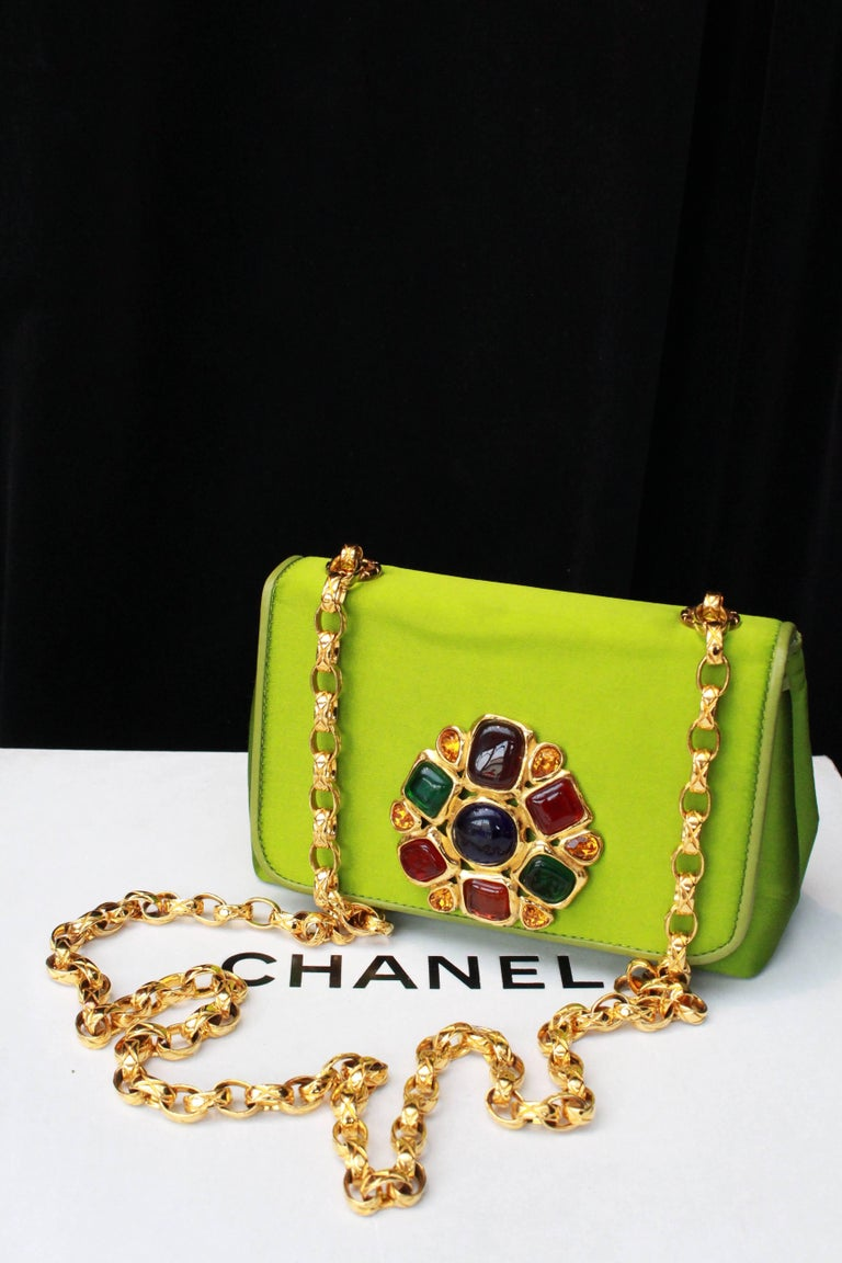 CHANEL (Made in Italy)  – Green satin jewel evening shoulder bag. The flap is embellished with a gilded metal jewel paved with ruby, emerald, sapphire and amber glass paste cabochons. The long gilded metal shoulder strap is made of quilted links.