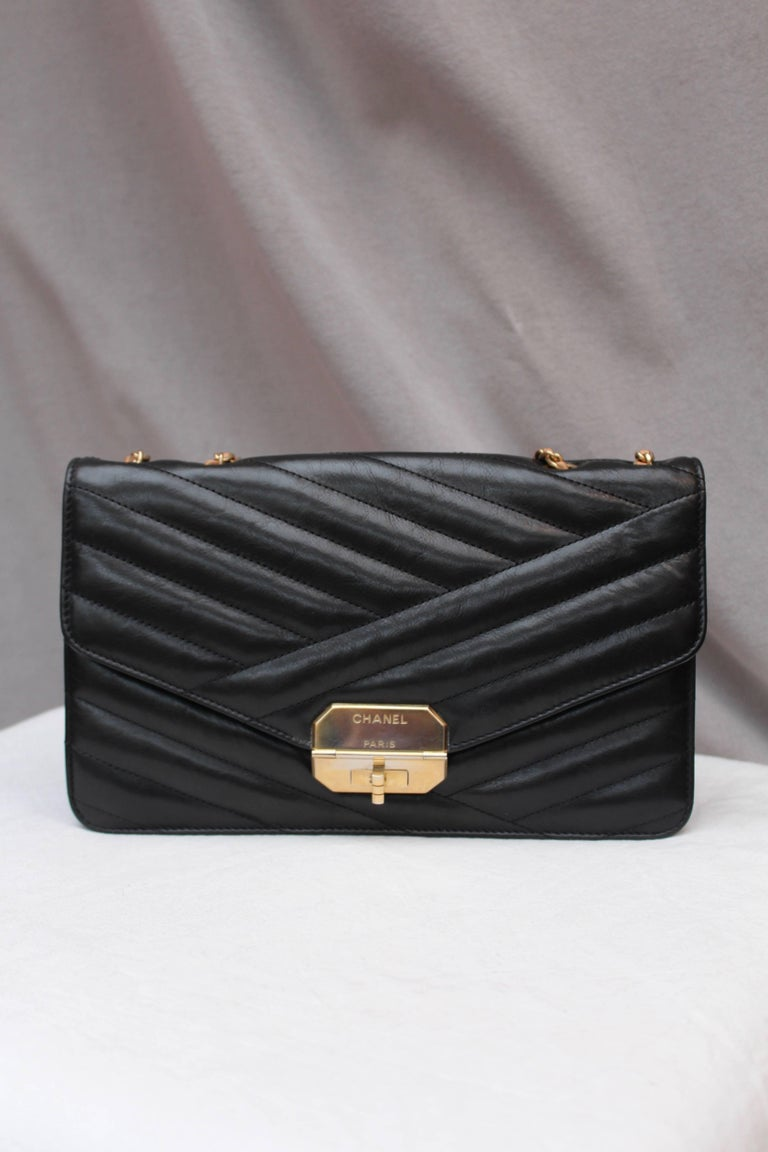 "CHANEL (Made in Italy) 2.55 model bag in quilted black leather with stripes pattern and gilded metal hardware. Brown leather and chain link sliding shoulder strap. The twist lock clasp reads ""Chanel Paris"". Black leather and beige canvas lining,"