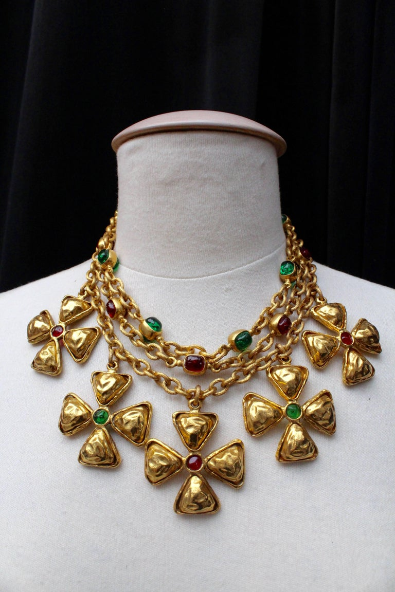 CHANEL (Made in France) Choker comprised of three strands of gilded metal chain decorated on the two shortest strands with emerald and ruby glass paste cabochons set in gilded metal.  Five pendants representing Maltese cross are hanging from the