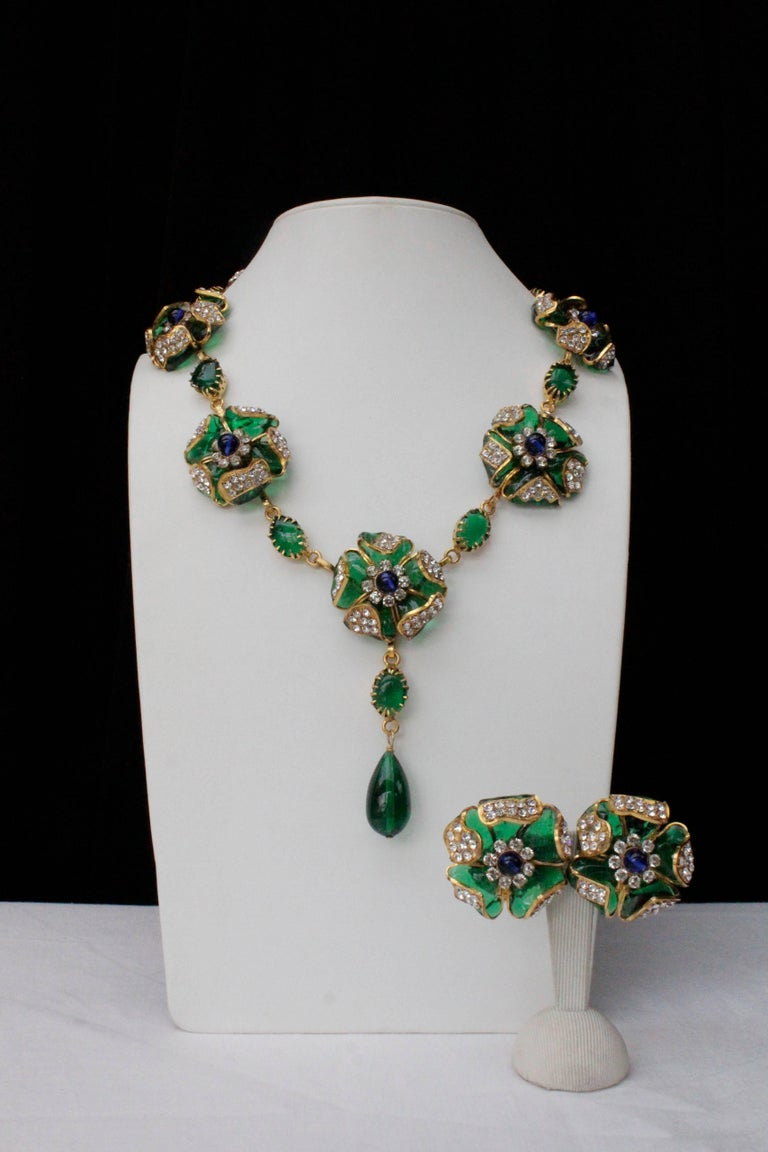 CHANEL (Made in France) Exceptional demi-parure comprised of a necklace and a pair of earrings. The necklace is composed of seven flowers separated by emerald oval glass paste cabochons finished with an emerald  tear-drop pendant. Each flower of the