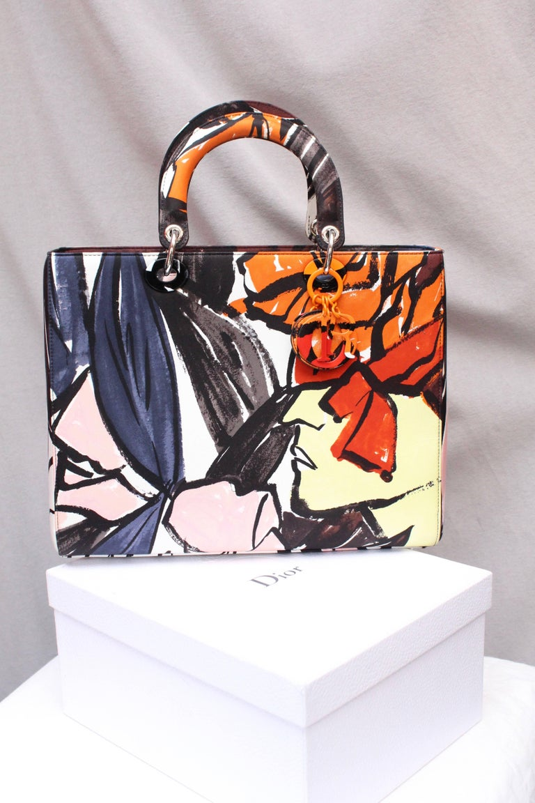 CHRISTIAN DIOR (Made in Italy) Large canvas Lady Dior Floral Graffiti Limited Edition by Raf Simons. It can be worn over the shoulder thanks to ots removable shoulder strap, or by hand. A colored metal key holder representing the brand initials