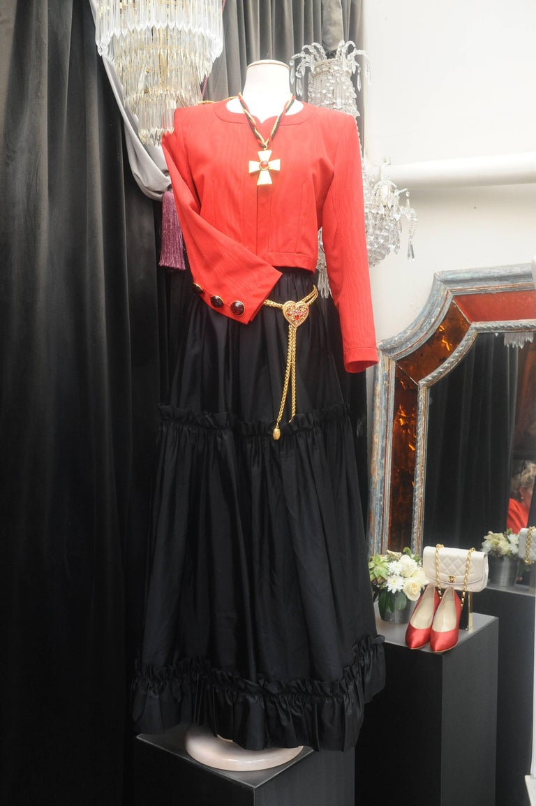 YVES SAINT LAURENT RIVE GAUCHE (Made in France)  Iconic set comprised of a short jacket and a long skirt.  The round collar jacket is made of red silk taffeta. Three red glass paste buttons set in gilded metal decorated the cuffs. Fuchsia silk