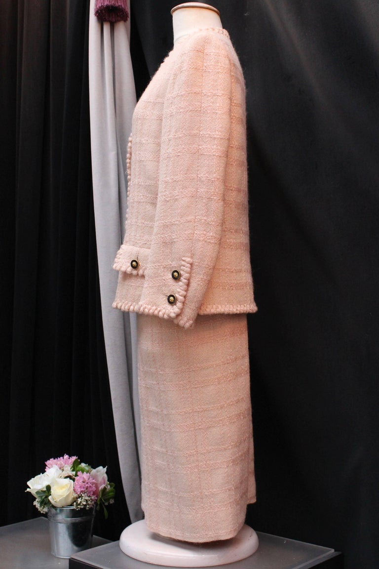 Chanel Haute Couture (Made in France)  Vintage light pink wool tweed set comprised of a skirt and a jacket.  The long sleeves V-neck jacket fastens with six round gilded metal and black resin buttons with a golden lion head in the center. The same