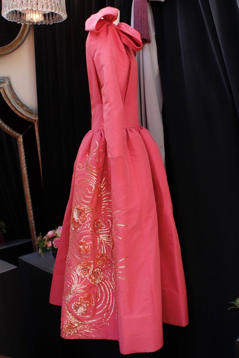 Nina Ricci (Made in France) Stunning opera dress composed of pink silk taffeta. The top features a close-fitting cut with a boat neck and long sleeves so tight they have a side zip at cuffs. The gored skirt is flared, from the waist to the ankles.