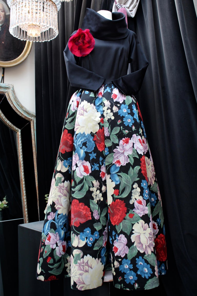 NINA RICCI (Made in France) Beautiful long sleeve evening gown composed of silk taffeta. The black close-fitting top features a wide large boat-neck that can be positioned in different ways thanks to some hooks at the back of the neck.  The generous