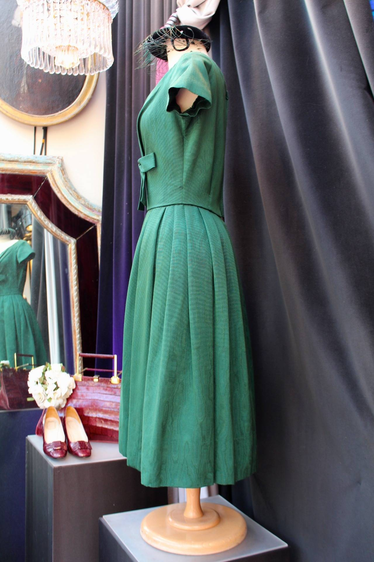 "CHRISTIAN DIOR BOUTIQUE (Made in France) Short cocktail dress in a ""New Look"" style composed of green thick silk adorned with a plunging neckline centered by a green bow. The dress is structured with short sleeves and a corolla skirt with an"
