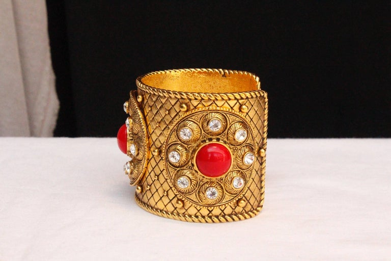 CHRISTIAN DIOR BOUTIQUE – Cuff bracelet composed of chiseled gilded metal decorated with three circles paved with rhinestones and a centered red cabochon.  Signed inside.  Circa 1990.  Wrist circumference 17.5 cm (7 in); Opening 3 cm (1.25 in);