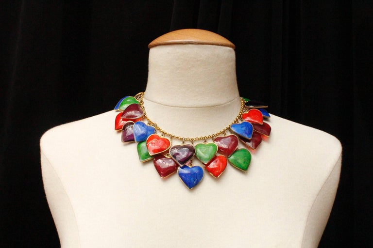 YVES SAINT LAURENT (Made in France) – Choker composed of a gilded metal chain embellished with thirty opaque or transparent glass paste hearts in green, blue, red and plum colors, set in gilded metal. The hearts are positioned in staggered rows.