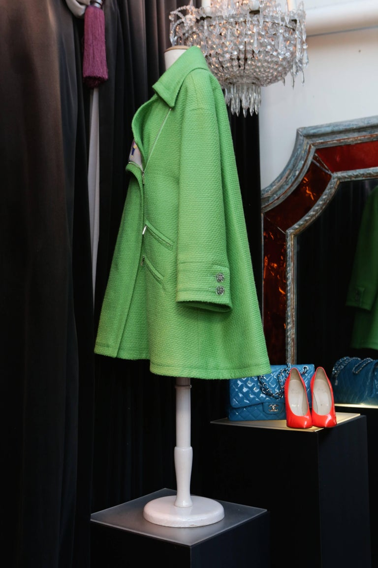 CHANEL (Made in France) Oversize apple-green wool coat withe a wide collar. Four side pockets with silver plated zip closure. The unique lining is made out of quilted silk printed with colored patterns in the style of Robert Delaunay's works and