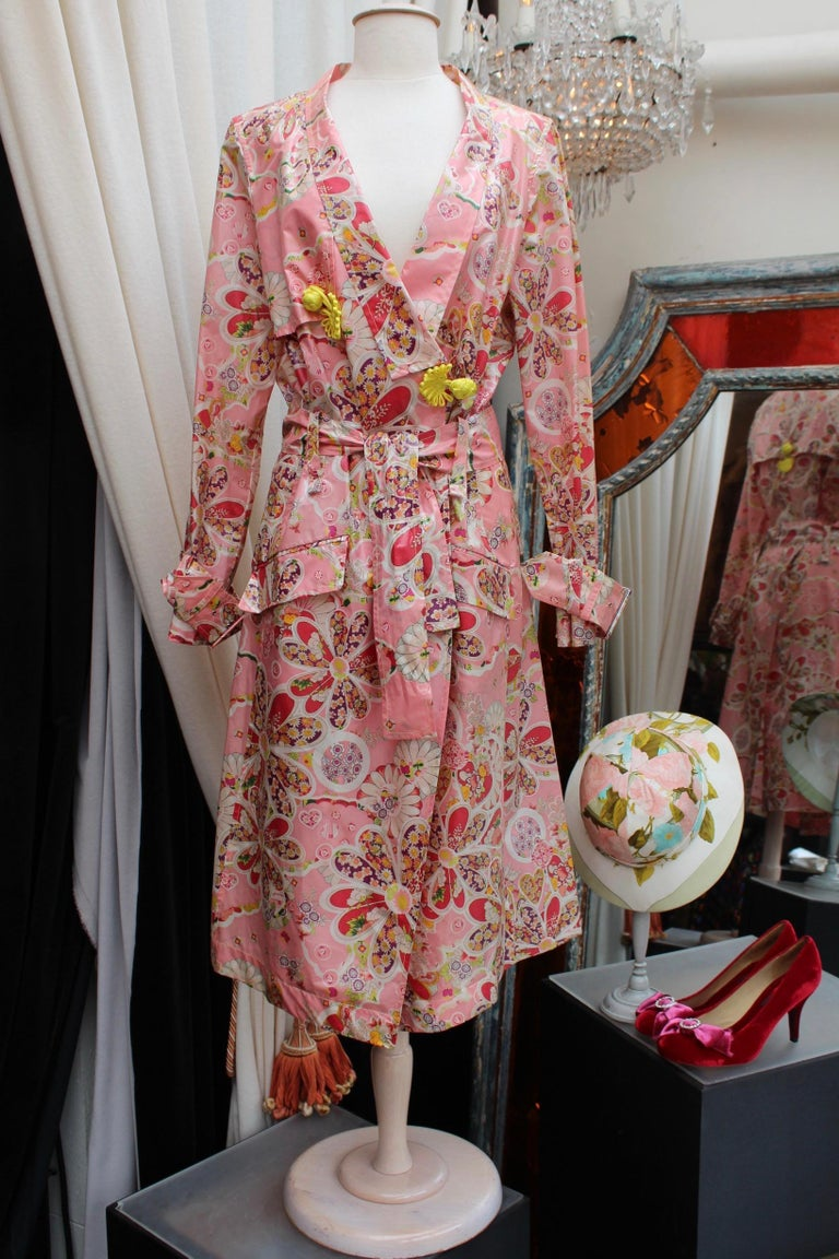 JOHN GALLIANO (Made in France) Gorgeous set comprised of a long trench coat and a high rise pair of flared pants. The set is composed of pink silk  with patterns representing cherries, hearts and flowers in a Japanese style, in yellow, purple, green