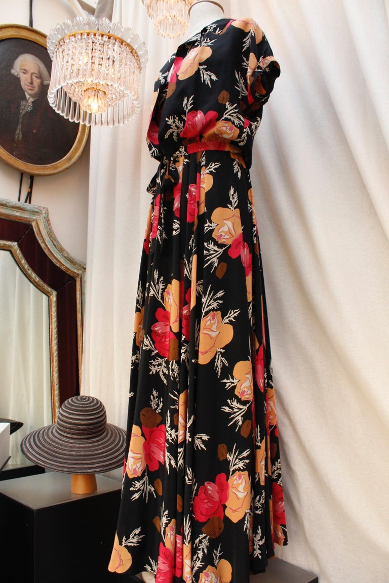 NINA RICCI (Made in France) Lovely long dress with shoulder straps, with a flared cut, a V-Neck, and pleats from the waist down. It is composed of black silk with floral pattern in orange, red, brown and white colors.  It closes with a side zip. It