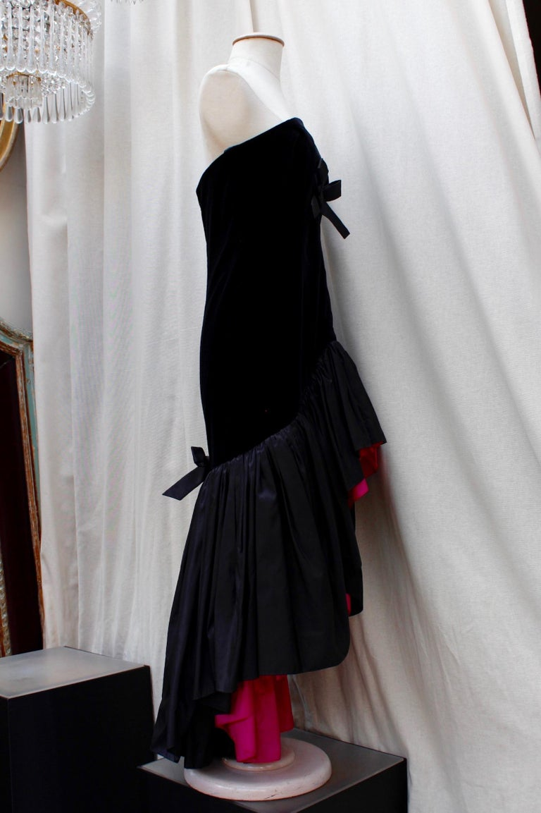 Yves Saint Laurent Rive Gauche (Made in France)  Exceptional bustier cocktail dress composed of layers of black tulle, in a 1950's style; it is cinched by a wide black satin bow and features a very feminine heart-shaped neckline.  The dress is