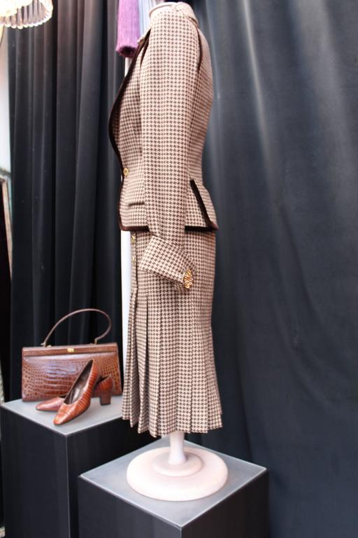 JEAN-LOUIS SCHERRER (Fall 2004-2005 Ready-to-wear) Long pleated dress and matching sleeveless jacket ensemble comprised of brown and ecru Houndstooth wool adorned with chocolate velvet galloon and large buttons.