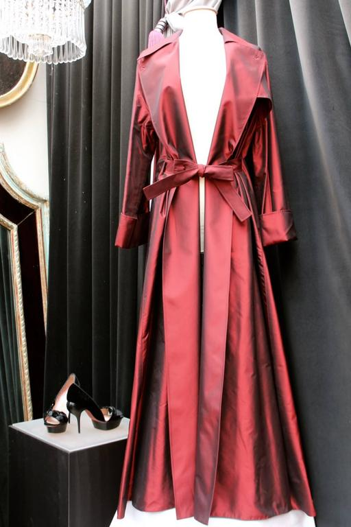 GUY LAROCHE COLLECTION (Paris) Large oversize trench coat in burgundy taffeta fastened with two buttons and a belt of the same fabric. 