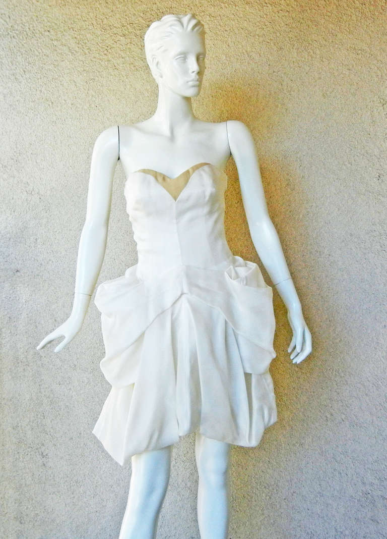 Alexander McQueen's pre death 2008 Collection  strapless bustier pouf dress.  Fashioned of off white silk organza draped in soft cascading folds creating a light high styled pouf skirt.  Corset interior with double zipper closure.