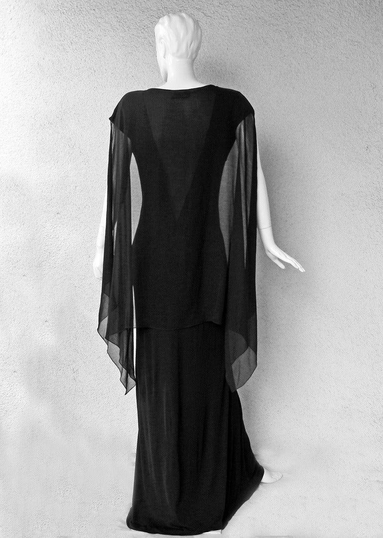 Dramatic goth black sleeveless gown with attached cape by Jean Paul Gaultier.  Fashioned of a weighty silk rayon with deep plunging sheer neckline and flowing sheer cape.  Offers concealed side pockets and an effortlessly drape to the body.  A