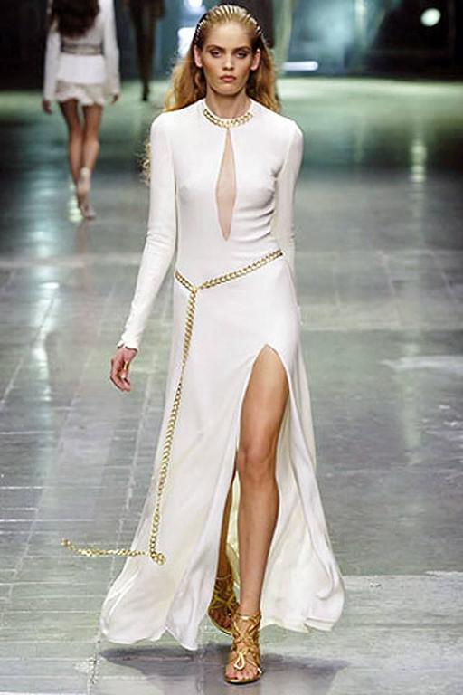 Alexander McQueen 2006 Winter white silk crepe gown with plunging net neckline.  Gold chain enhancements with sexy thigh high slit. Long slender sleeves with wrist zippers.   Fully lined. Back zipper closure.