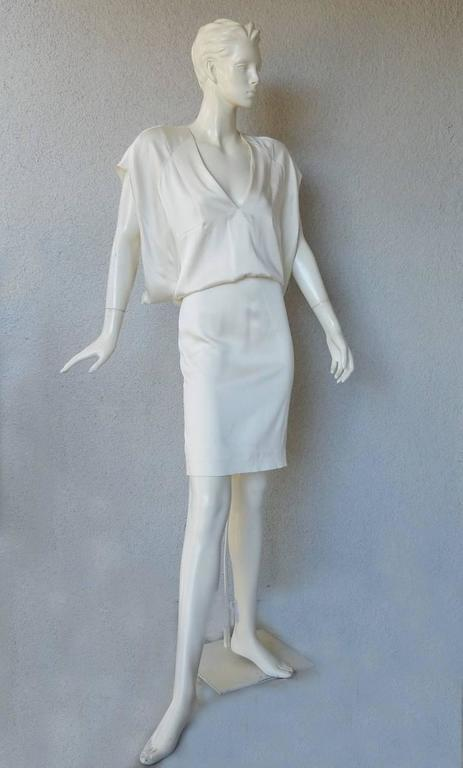 Tom Ford Winter white silk evening dress. Features plunging neckline blouson bodice, form fitting skirt and back kickpleat. Modesty panels on each side of interior bodice. Long dramatic keyhole back. Back zipper closure.  Size: 38; Bust: to 34