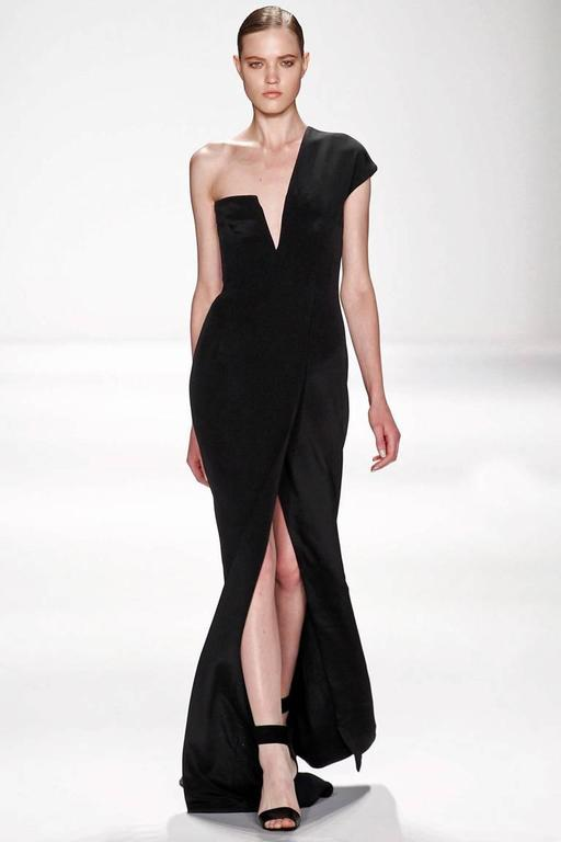 KaufmanFranco black silk gown designed with stunning visual appeal.   Boasts lined and padded interior bonded bodice with side zipper closure.  Lightly draped skirt with high front slit. Back features inverted V nude net panel.  Dress is identical