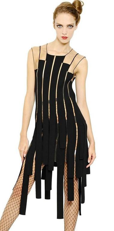 Jean Paul Gaultier body hugging ribbon dress fashioned of rayon and poly with a bit of stretch.   Features nude net look shoulder treatment extending into uneven strips down the body of the dress.  Simple over head easy slip on. 