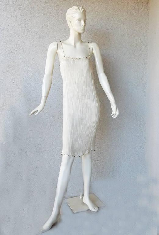 1999 John Galliano, for the House of Dior, designed a homage to Mariano Fortuny collection. This Delphos dress fashioned of accordian pleated eggshell white china silk in the fashion of the original Fortuny Delphos.  Glass beads trimmed at neckline,