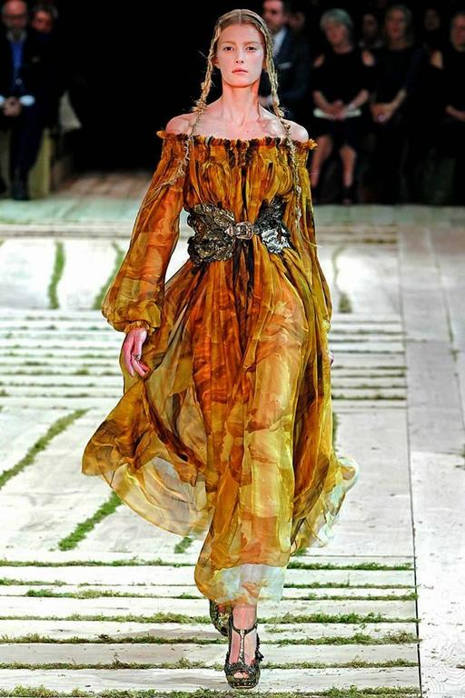 Alexander McQueen romantic silk chiffon off-the-shoulder gown.  Fashioned in warm shades of gold frond print cinched at waist with belt. Hand pleated and smock detail throughout. Neckline designed to be worn on or off shoulders as seen in runway