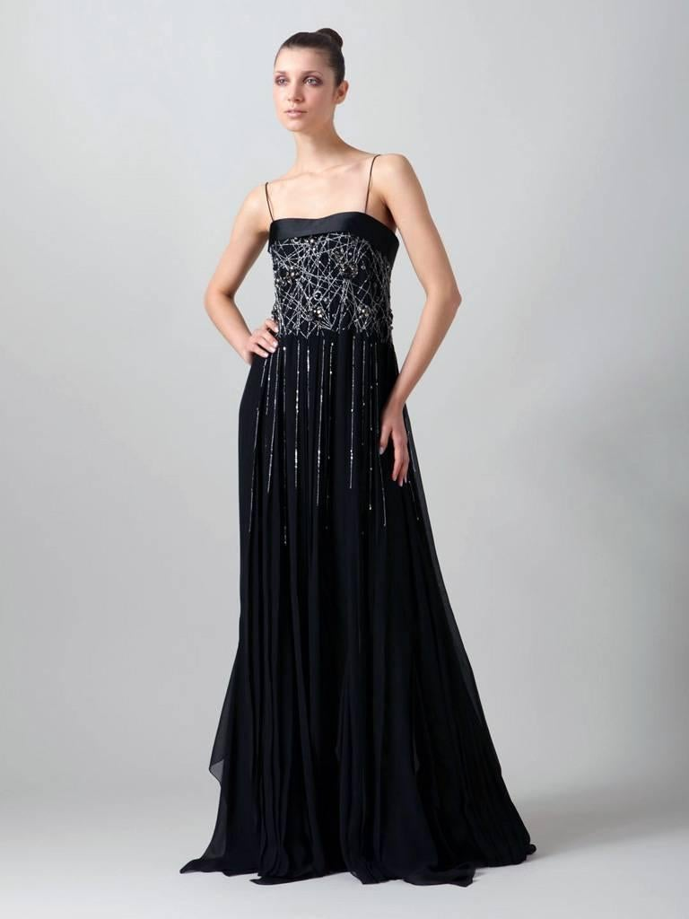 A bold and dramatic look from Gianfranco Ferre. Strapless (incl straps if desired) gown fashioned of black silk chiffon featuring hand beaded sequins, and jewel applique both front and back bodice.  Bodice  has interior boning, molded cups and back