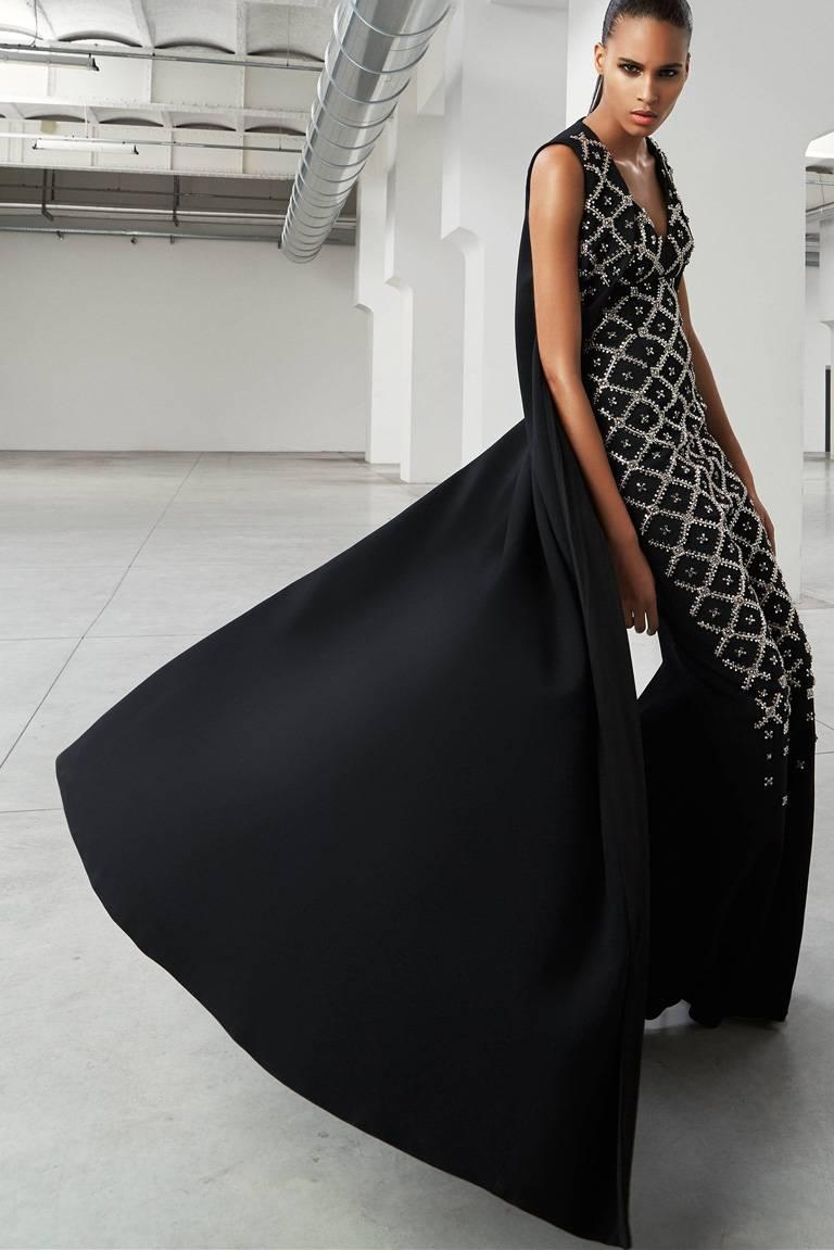 """Antonio Berardi """"Finale"""" gown from the fall 2015 Collection.  Dress fashioned of weighty black fabric with """"V"""" neckline adorned  with hand embroidered crisscross metal stud embellishment.  Its attached long vest is partially embellished.  Fully"""