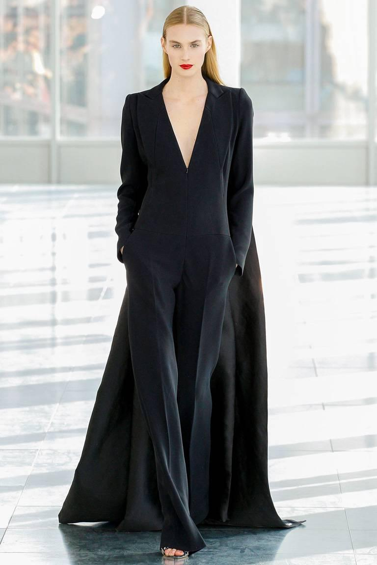 "In this 2013 ""Finale Tuxedo Jumpsuit with Train"" is a design inspired by the tabard cady gown which is a signature silhouette that Antonio Berardi does remarkably well.     Jumpsuit fashioned as a tuxedo inspired creation with attached long wide"