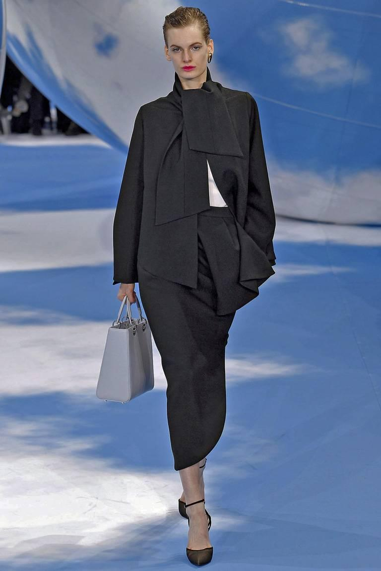 Christian Dior 1950's inspired haute couture stylish suit by Raf Simmons for the Fall 2013 collection.  Stunning suit was look #1 which opened the show.  Fashioned of fine black wool constructed with a tie neckline; swing jacket with bell sleeves.