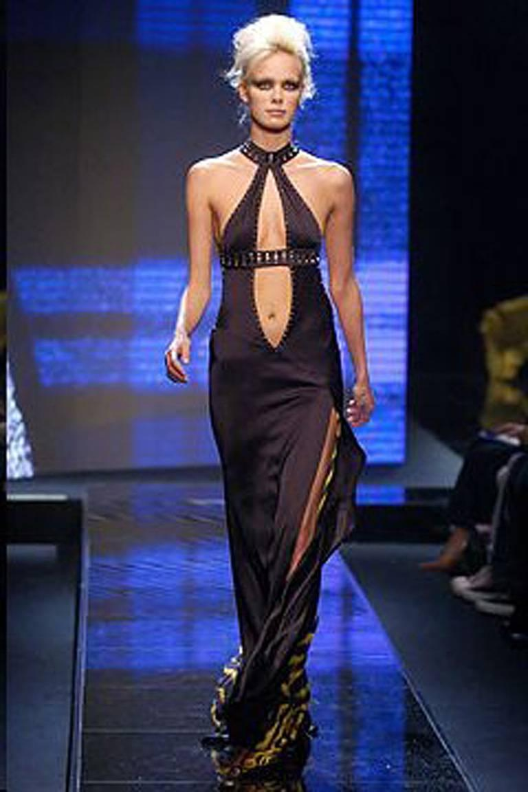 Early 2000 Versace cut-out halter gown with thigh high slit and plunging neckline.  Trimmed with square faceted silvertone grommets.  Bias cut with asymmetric open back with long full tiger print panel.  Zipper closure.  Uniquely designed and