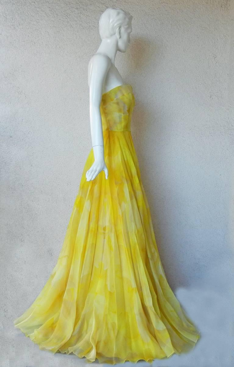 Stunning Alexander McQueen gown fashioned of layers of silk organza. Strapless fitted bodice extends into a voluminous ballgown skirt.  Designed in a rich daffodil yellow ground overlaid in a large floral poppy pattern.    Ideal for the flowering