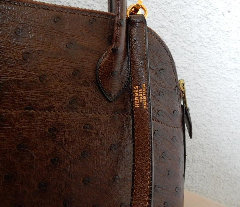 Elegantly designed authentic Hermes genuine ostrich bolide bag in a rich shade of brown. Features gold metal hardware; two (2) rolled top handles; brown leather lining; one interior slit pocket,  with matching detachable shoulder strap.  A