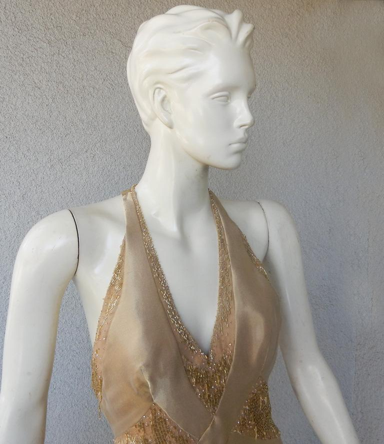 Atelier Versace custom-made beaded gown fashioned of golden champagne gossamer silk.  Gown features halter sweetheart neckline, corset interior boned bodice,  open T-back; fully lined and back zipper closure.  Further enhanced by panels of dripping