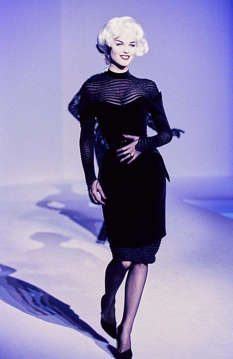 Autumn-Winter 1995-96 Thierry Mugler black velvet dress with transparent knit. Form fitting bodice cinched waist with matching black velvet belt. Dress is identical to that in the photo of the book