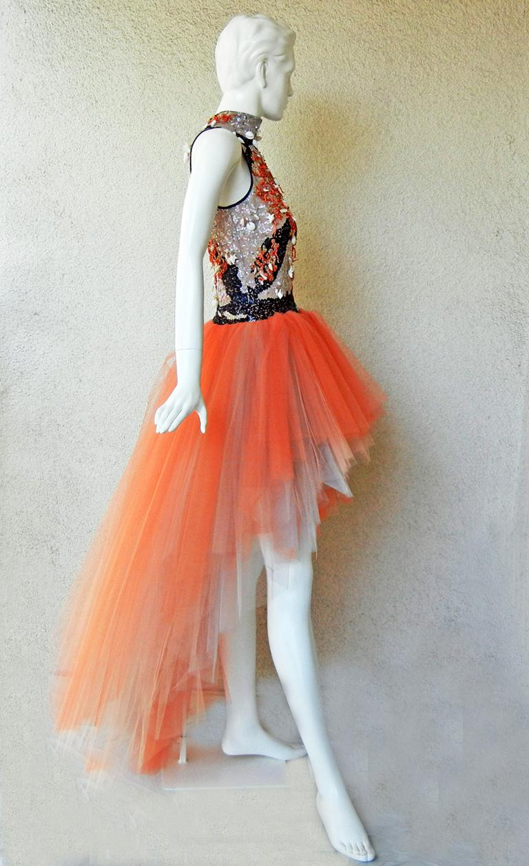 Rare 1970's Valentino high low evening dress a style of which very few were produced.   Bodice displays Valentino's superb beaded handwork of hanging shells, coral, and seed beads. Black satin trim at neckline and armholes.    Ombre tangerine tulle