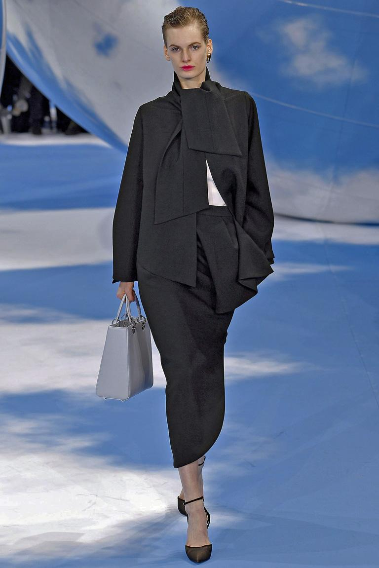 Christian Dior 1950's inspired haute couture stylish suit by Raf Simmons for the Fall 2013 collection.  Stunning suit opened the runway show as look #1.  Fashioned of fine black wool constructed with a tie neckline; swing jacket with bell sleeves.