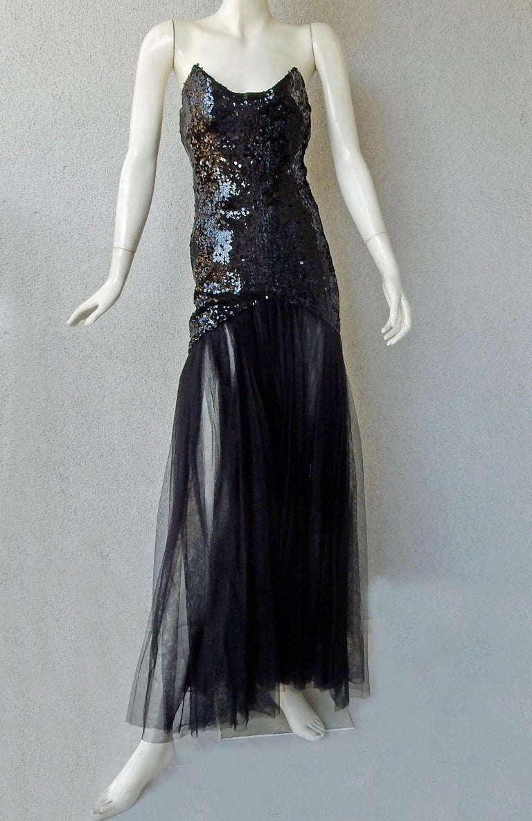Rare mid 90's Thierry Mugler strapless mermaid style evening gown with elongated bodice of handsewn black paillettes and skirt fashioned of layers of black chiffon.  Lined.  A very dramatic look and the essence of the designer's work. Fully lined;