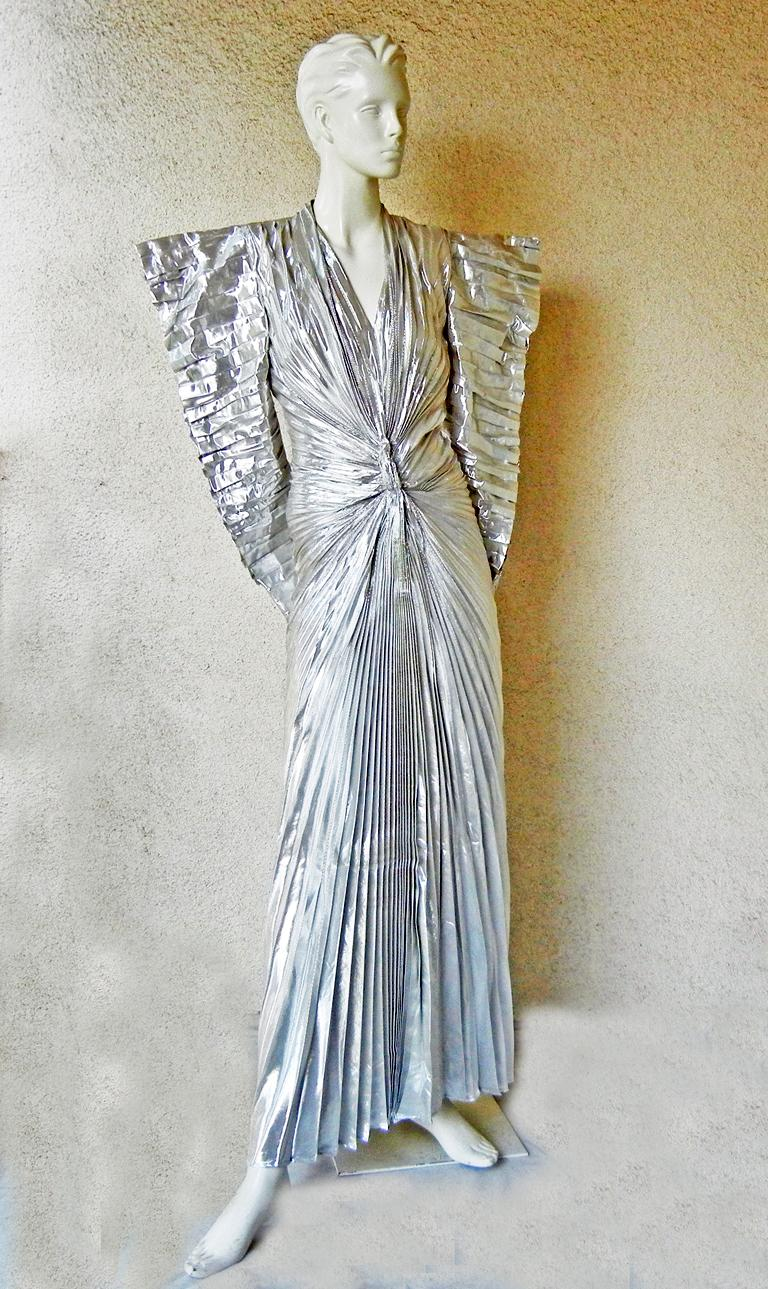 Thierry Mugler's 1979 pleated silver lame futuristic dress with wide padded stand-away shoulders, horizontally pleated sleeves with zippers, pleats converging below plunging V-neck in a sunburst design at midriff. The back is fitted over hips, then