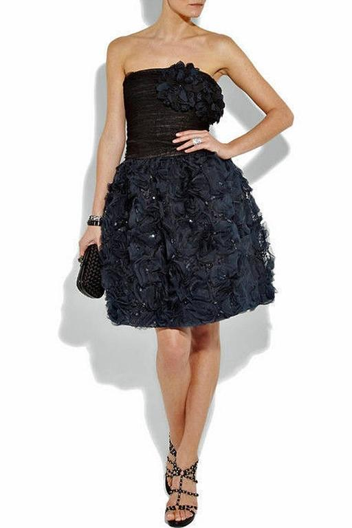 Oscar de la Renta strapless lace and silk corsage cocktail dress.  Hand ruched black lace bodice with large attached rosette corsage.   Bodice extends into navy blue tulip skirt adorned with rosettes and twinkling sequins.  Back zipper closure;