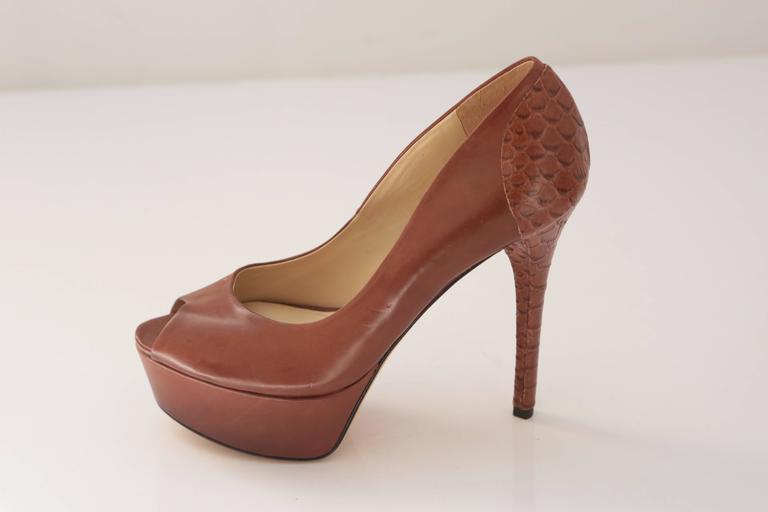 Brown leather peep toe platform heel with embossed snakeskin sculptual heel. A classic silhouette for any occasion.