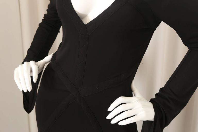 YSL black dress with bell sleeves with open back, stitching detail, v-neck and open back.