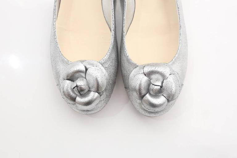 Chanel silver flats with rosette, round toe and small heel.  W/ Box
