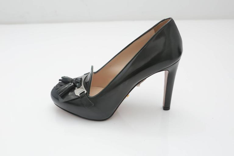 """Prada patent leather green pumps with 4"""" heel, tassels, front logo and silver placket. Gold """"Prada"""" placket on bottom."""